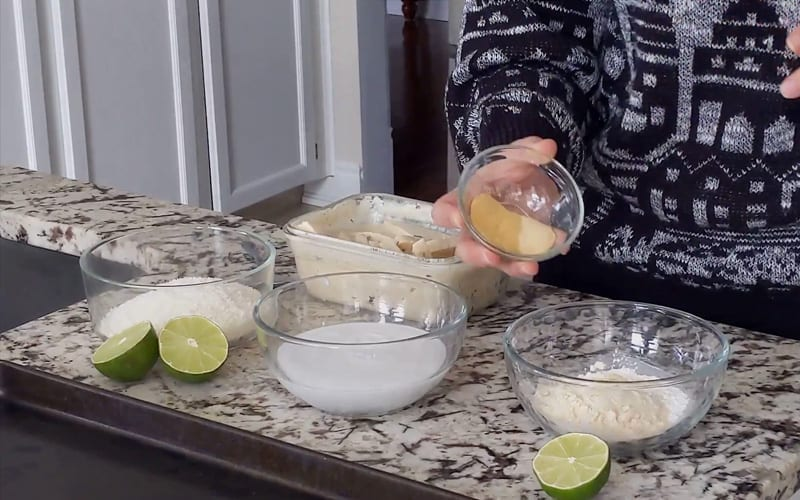Ingredients to prepare coconut crusted tofu breading, including starch, coconut flour, and onion and garlic powder. These ingredients are combined into one bowl while two other glass bowls contain other ingredients needed for coating the tofu.