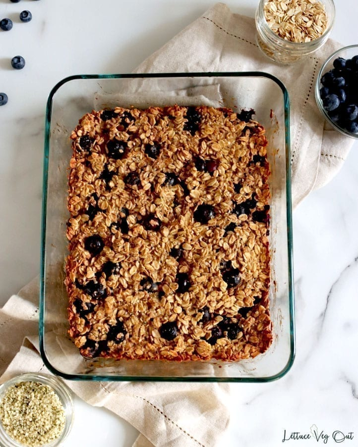 A glass baking dish full of blueberry baked oatmeal made with vegan ingredients. Around the baking dish are some of the recipe ingredients, including rolled oats, blueberries and hemp seeds.