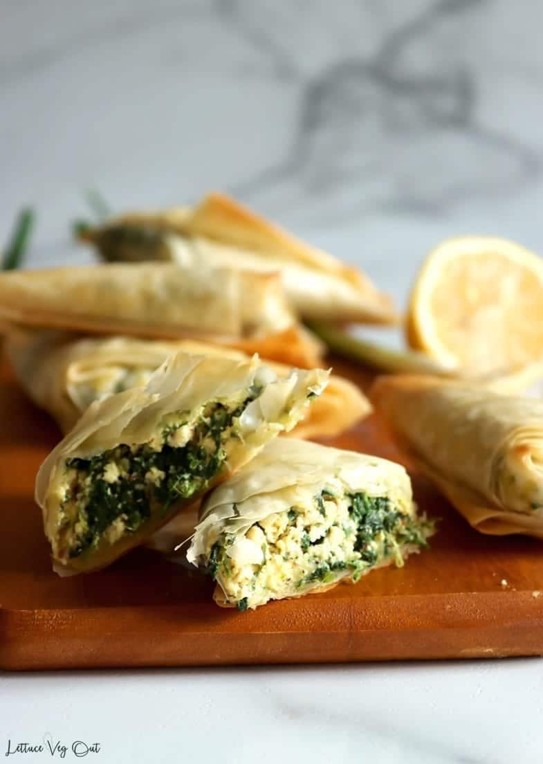 A close-up image showing vegan spanakopita on a wooden serving board. One triangle is cut open while the others remain whole.