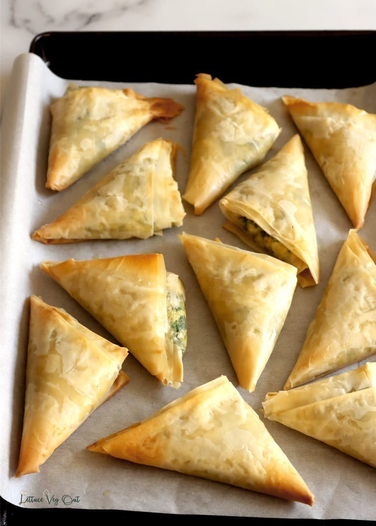 Baked spanakopita triangles that have been removed from the oven but are still sitting on a parchment paper-lined baking sheet