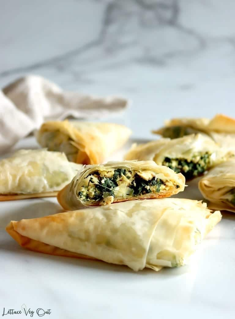 Crispy, golden-brown vegan spanakopita triangles with a couple cut open to show their tofu spinach filling