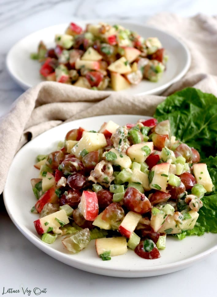 Two white plates with heaping piles of vegan Waldorf salad. The front plate has salad spread out over large leaves of romaine lettuce