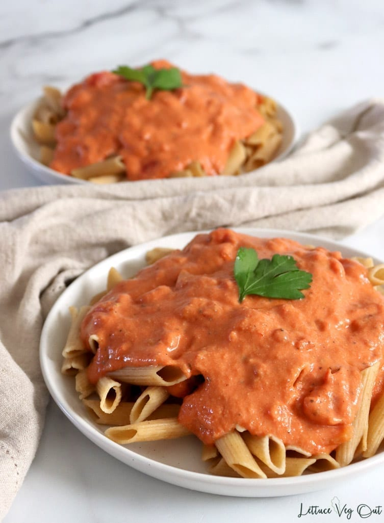 Two plates of penne alla vodka using vegan vodka sauce
