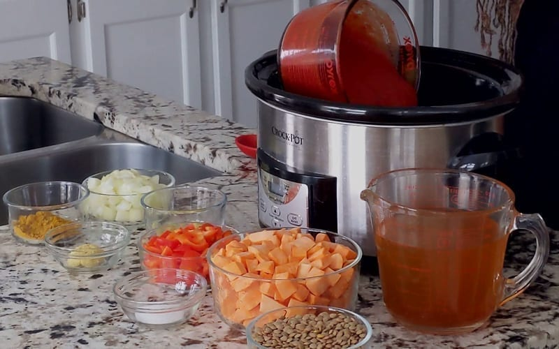 Begin adding the curry ingredients to your slow cooker, starting with crushed tomatoes. All ingredients are prepared and ready to add in.
