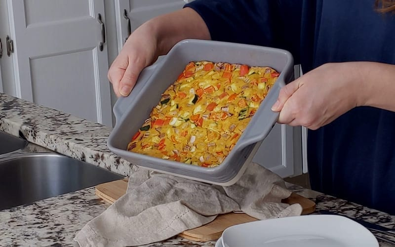 A close-up image showing the baked tofu frittata with pieces of zucchini, red bell pepper and red onion at the top. The frittata has baked into a deep yellow color that resembles eggs.