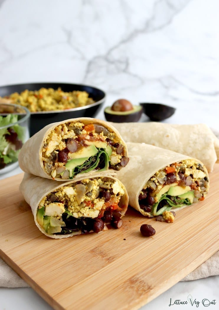 Three burrito halves stacked on wooden board with full burrito in back along with blurred bowl of salad greens, black pan filled with tofu scramble and two avocado halves.