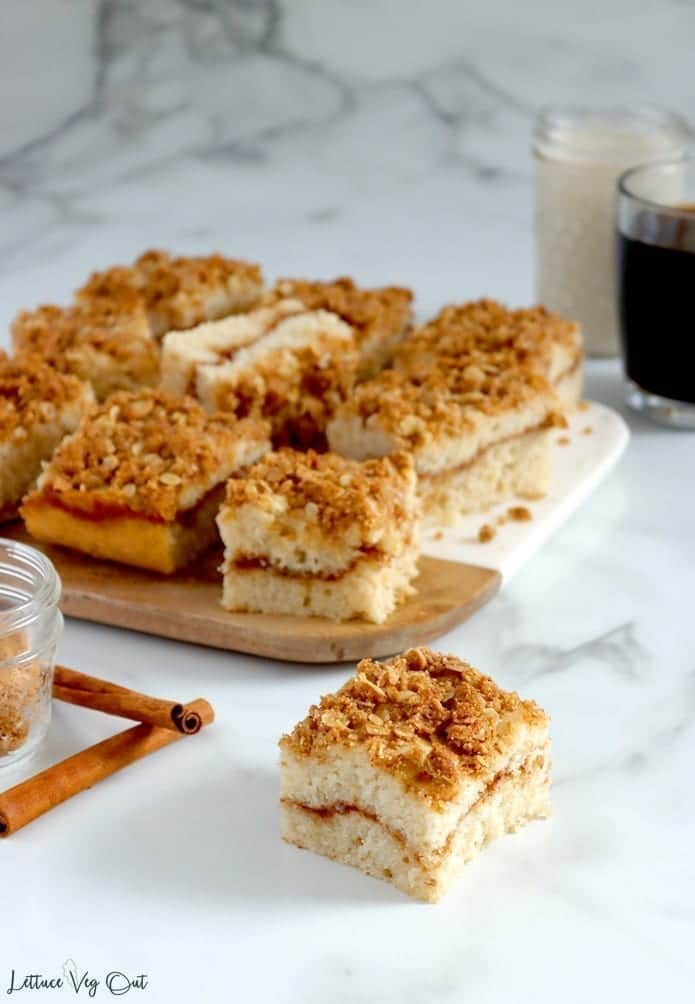 Square piece of vegan coffee cake with cinnamon streusel sitting on marble counter top with crossed cinnamon sticks set to the left. Behind is a half wood half marble board topped with nine other pieces of cake with the center piece on its side. To the back right sits a small mason jar of milk and clear mug of black coffee.