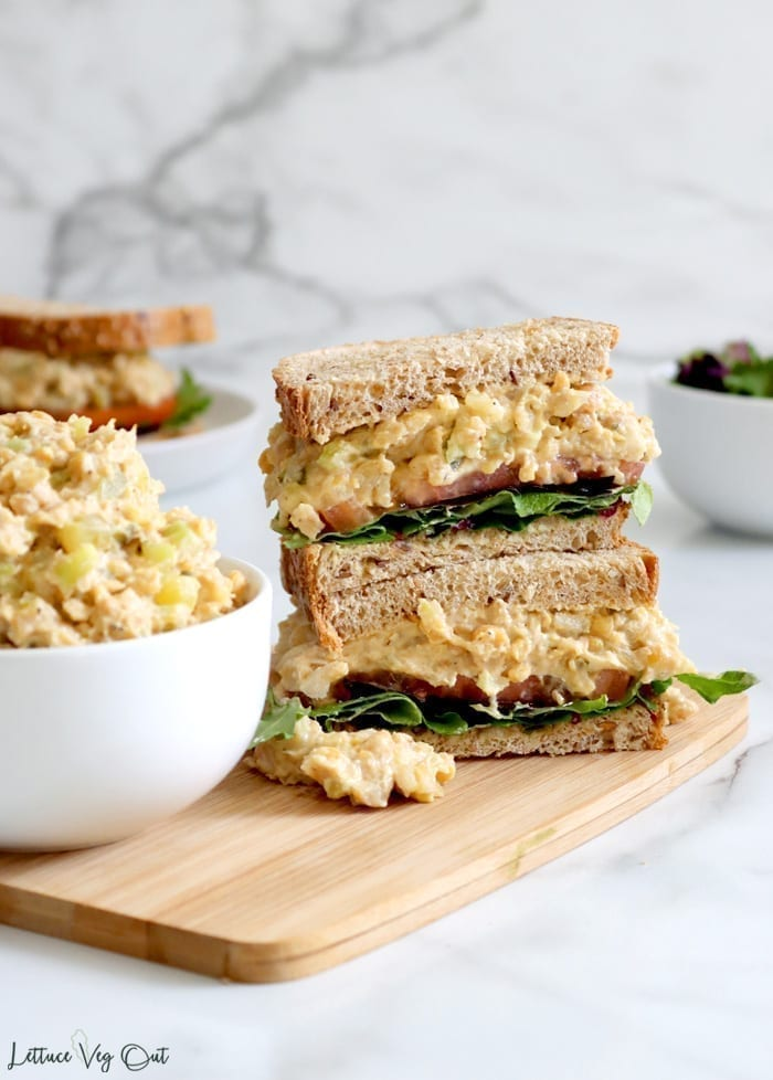 Sandwich cut in half and stack on wood board with white bowl of chickpea salad next to it. Sandwich made with brown bread and filled with mashed chickpeas, tomato and lettuce. Blurred sandwich in back left.