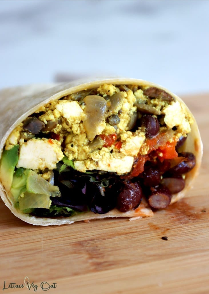 Half of a breakfast burrito filled with tofu scramble, black beans, leafy greens, avocado and salsa; sitting on wooden board.