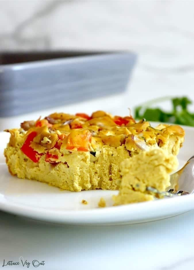 A piece of vegan tofu frittata sits on a white plate with a fork full of tofu egg ready for the first bite. The top of the frittata shows zucchini, red pepper and red onion