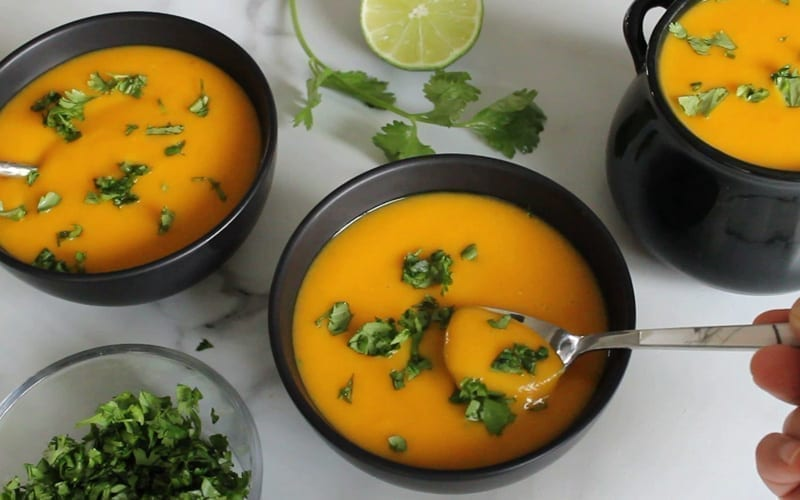 Three served bowls of vegan pumpkin coconut soup with chopped cilantro spread on top for garnish.