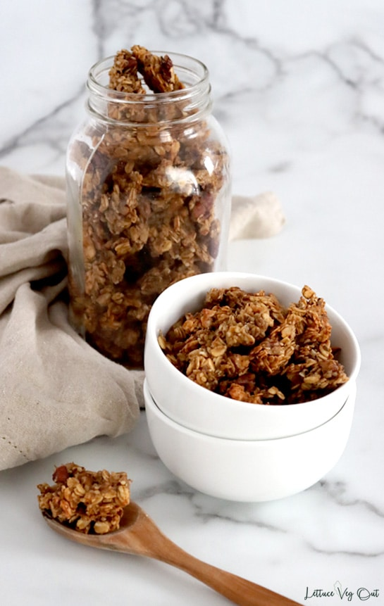 Two stacked white bowls filled with granola nut clusters in front of jar filled with granola. Light brown towel wraps around the jar and the top of a wood spoon with granola on it sits in front of the bowls with most of the spoon handle cropped out.