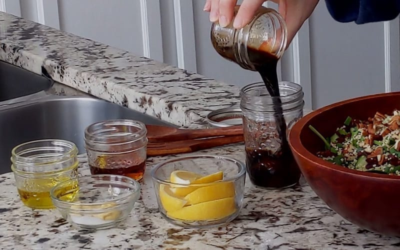 A very small glass jar containing balsamic vinegar pours into a slightly larger glass jar. Beside this are additional glass jars of olive oil, maple syrup and Dijon mustard. Together these ingredients create a flavorful maple balsamic dressing