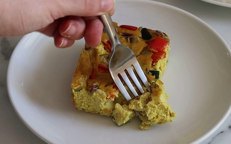 A close-up image of served tofu frittata. A soft, flaky texture is visible in the frittata, while pieces of bell pepper, zucchini and red onion poke up through the top of the piece