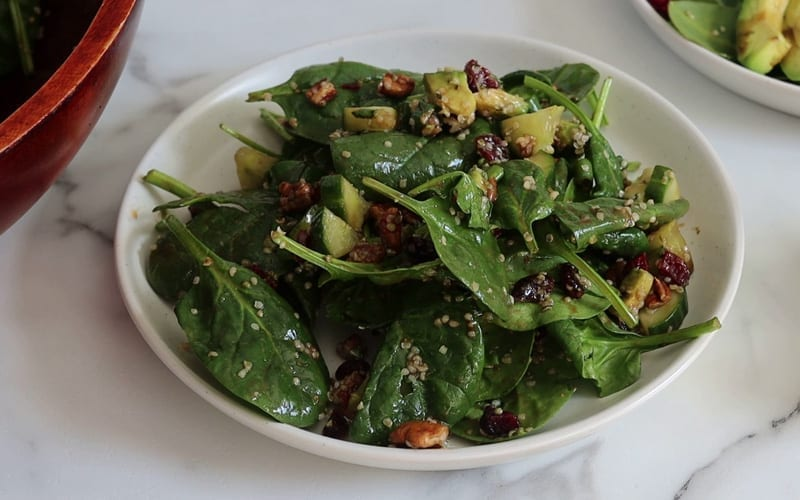 A served plate of vegan spinach salad showing many of its ingredients including dry cranberries, cucumber and hemp seeds
