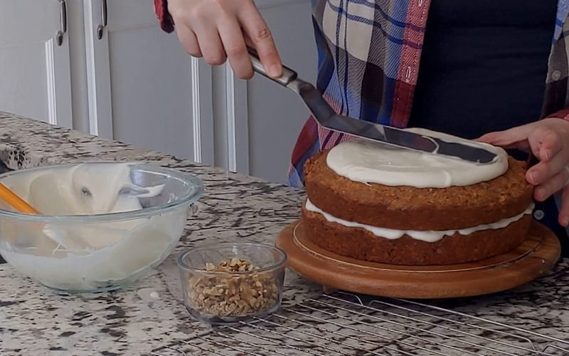 Spreading dairy free vegan icing onto a carrot cake made with pineapple. A small glass jar with walnuts sits beside, ready for adding to the top of the cake