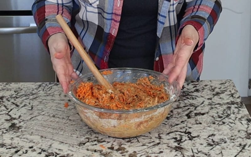 A large glass bowl full of mixed batter with carrots and walnuts added.