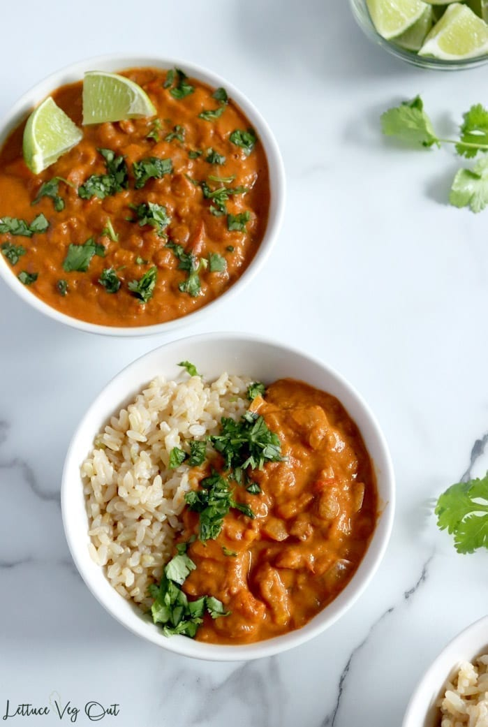 Crock pot sweet potato and lentil curry served into two large white bowls. Cilantro and lime wedges garnish both bowls, while extras sit in small glass dishes on the granite countertop