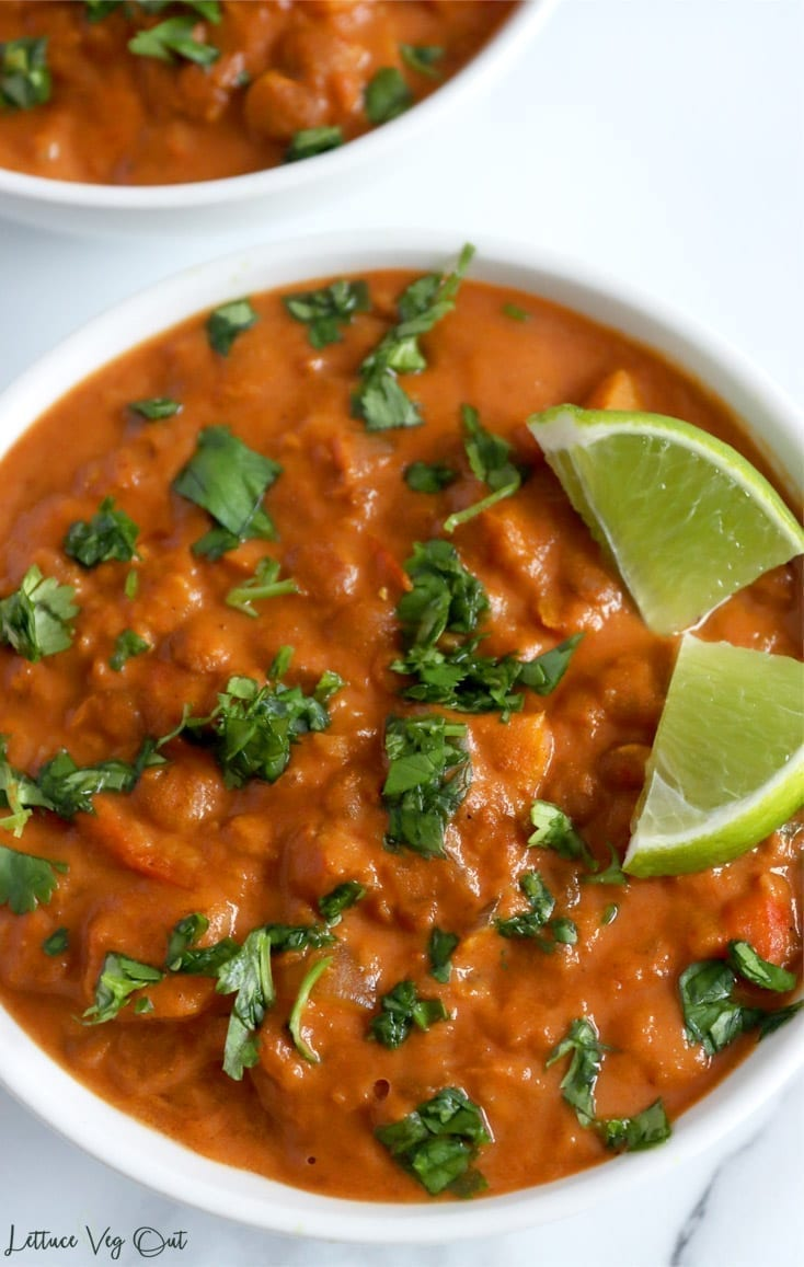 A close-up image showing the color and texture of vegan slow cooker curry made from sweet potato and lentils. The deep orange color is contrasted by chopped green cilantro which is sprinkled across the top of the entire bowl