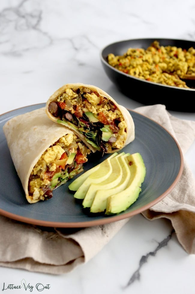 Burrito cut in half and stacked up on blue plate with avocado slices resting in front of burrito. Plate sits on light brown towel and a pan filled with tofu scramble is blurred to the back right.
