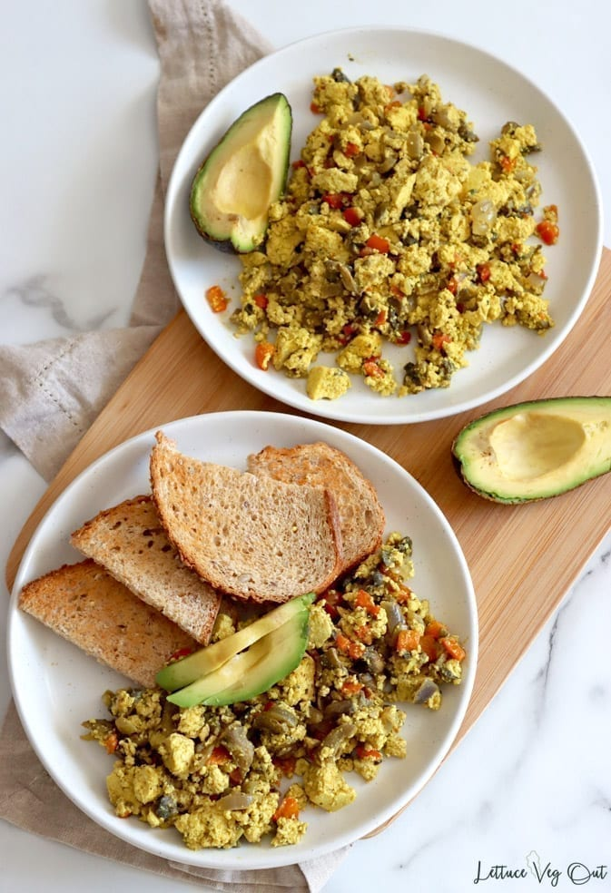 Top view of two white plates sitting on a wood board over a light brown towel. Each plate has crumbled, scrambled tofu cooked with vegetables on it, along with a quarter avocado and the lower plate also has four slices of whole grain toast.