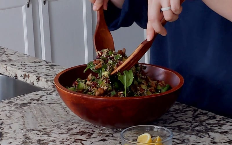 Tossing together the ingredients for a vegan spinach salad in a large wooden serving bowl. A salad spoon and fork gently combine ingredients while lemon wedges wait to be added on top
