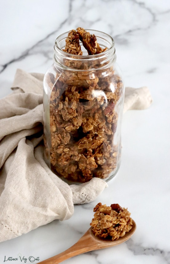 Large glass mason jar filled with banana nut granola set on a white marble background. A light brown towel is wrapping around the left side of the jar and a wood spoon full of granola is resting on the marble in front of the jar.