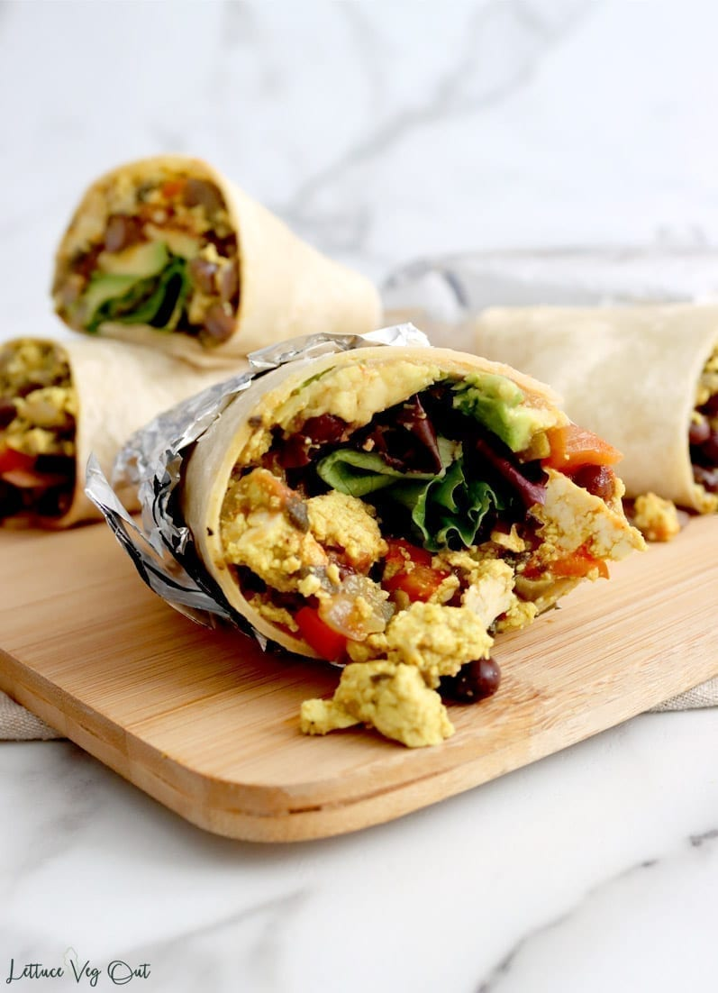 Cut open burrito wrapped in tin foil filled with tofu scramble, lettuce, black beans, avocado and salsa sits on wood board surrounded by other burrito halves.