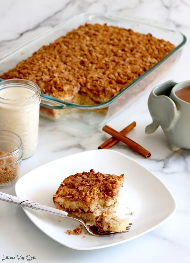 White plate with slice of coffee cake and forkful of cake in front of the slice sits in front of a slightly blurred background including two crossed cinnamon sticks in the center, a small mason jar of soy milk and even smaller jar of cinnamon sugar to the left, a grey elephant shaped mug filled with lightened coffee to the right and a large glass baking tray filled with cake minus one slice in the center back.