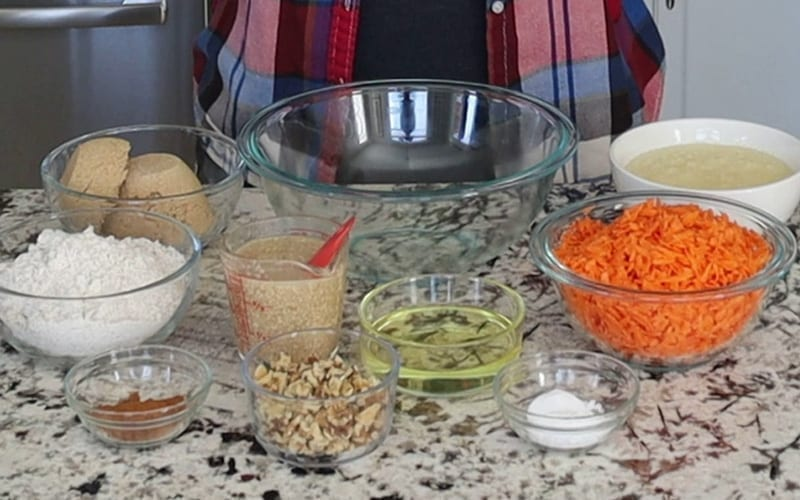 Ingredients to make a vegan carrot cake with pineapple and walnuts, including oil, sugar, cinnamon and flour
