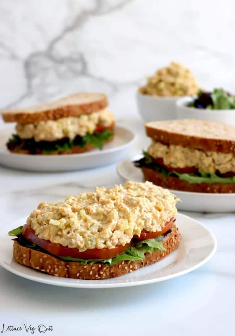Three plates with only front on in focus which has open face sandwich of grainy bread, lettuce, tomato and mashed chickpea salad. Other plates with sandwiches plus two bowls in far back filled with chickpea salad and lettuce.