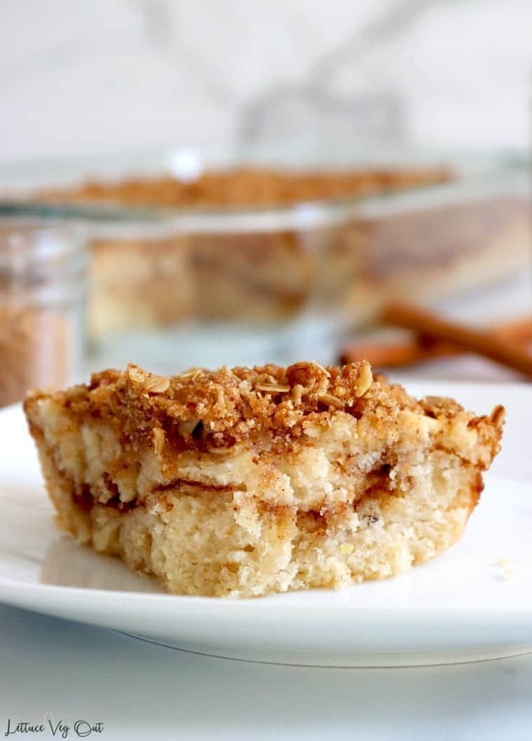 Close up of cinnamon coffee cake slice sitting on white plate. Blurred cinnamon sticks, glass baking tray filled with remaining cake and small glass jar sit blurred in background.
