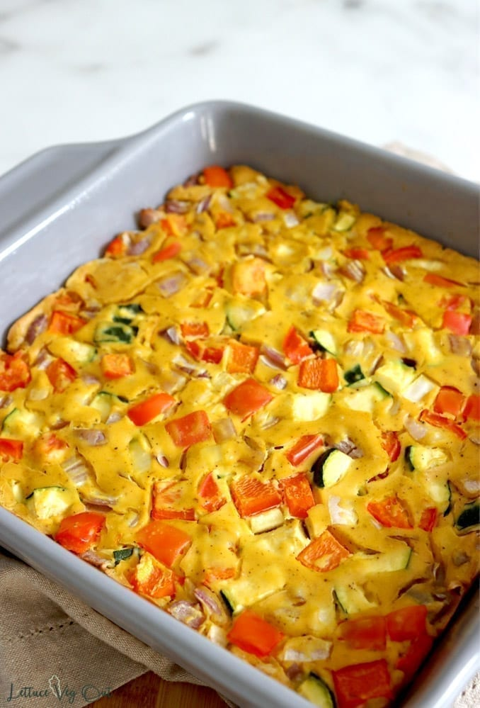 A close-up photo of vegan breakfast frittata in a square grey baking dish. The top of the frittata in speckled with vegetables including red bell pepper, red onion and green zucchini