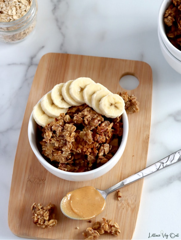 Top view of a bowl of granola clusters with sliced banana resting along the top side of the bowl. Other granola clusters set on wood board around bowl and a spoon filled with peanut butter rests in front of bowl.