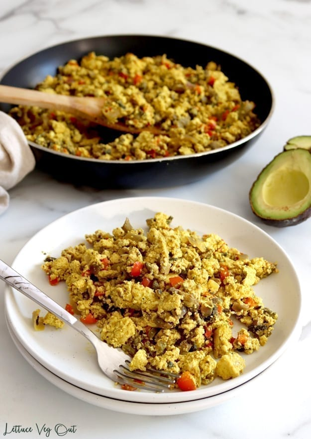 Vegan scrambled eggs made from crumbled tofu and cooked with mushrooms and red pepper piled on a double stack of white plates with a fork. A pan with more scramble sits in the back with half an avocado.