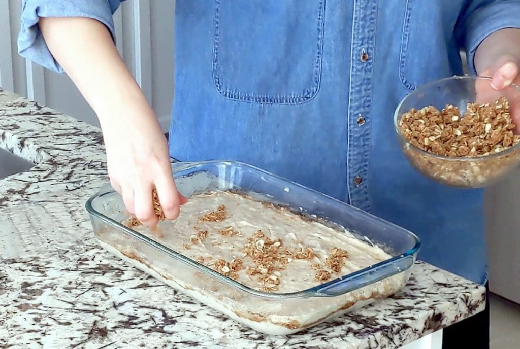 A person wearing a blue denim shirt stands behind a marble counter top with a large glass baking dish on top. One hand holds a glass bowl of streusel while the other sprinkles a handful of streusel onto the top of the raw cake batter in the dish.