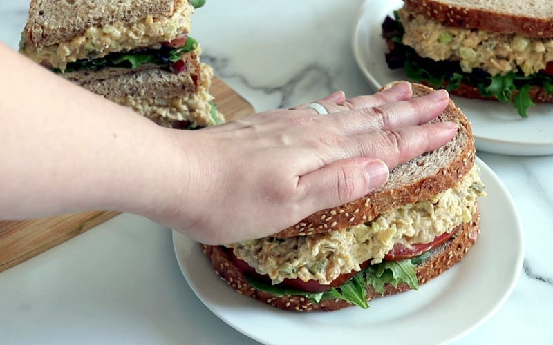 A hand presses a piece of bread onto the top of a sandwich filled with lettuce, tomato and mashed chickpeas. The sandwich is on a white plate with a second sandwich on plate in the back right corner. In the back left corner sits another sandwich, cut in half and stacked up on a wood board.