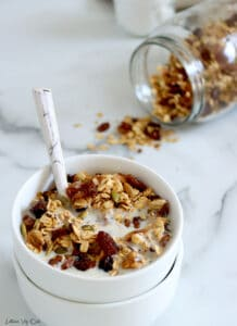 A double stack of small white bowls is filled with muesli (oats, raisins, cacao nibs and pumpkin seeds visible) with milk and a spoon in the bowl. To the back right corner, a large mason jar is tipped on its side with a sprinkle of muesli falling out of it.