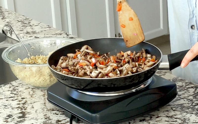 A single element electric burner with a large black frying pan on top filled with raw chopped mushrooms, red pepper and red onion. A large glass bowl filled with crumbled, spiced tofu sits partially hidden behind the pan to the left. A hand holds the handle of the pan and a wood spoon hovers over the contents of the pan.