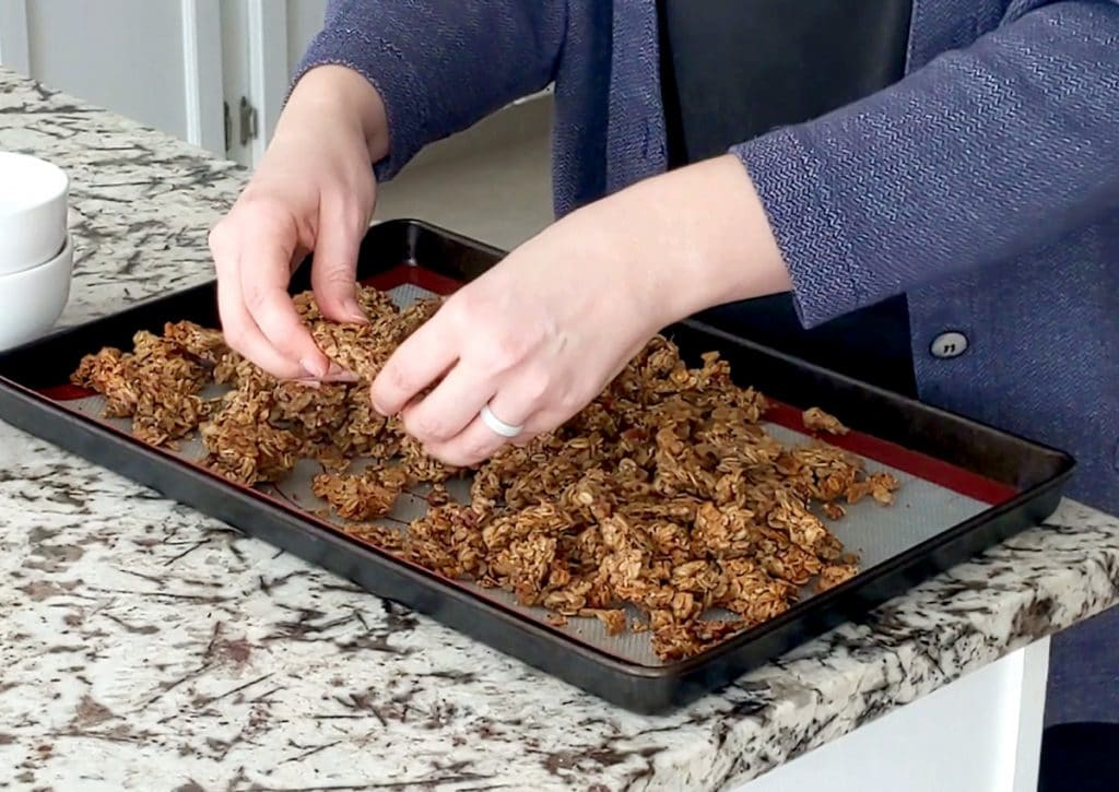 Hands crumbling pieces of granola on a baking tray that is lined with a silicone mat. Baking tray on a marble counter top.