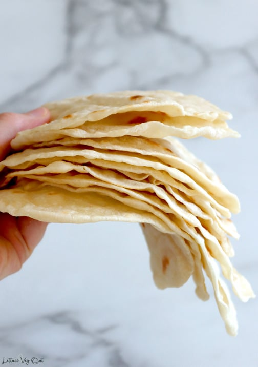 Hand holding stack of flour tortillas in front of grey marble backdrop; tortillas are curving down where the hand isn't supporting them.