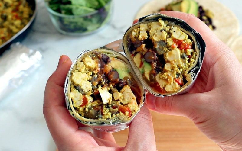 Hands holding up a burrito that is wrapped in tin foil and cut in half showing the inside full of crumbled tofu, black beans, avocado and salsa. A wood board, tortilla wrap, glass bowl of salad greens and pan with tofu scramble in it sit blurred in the background.
