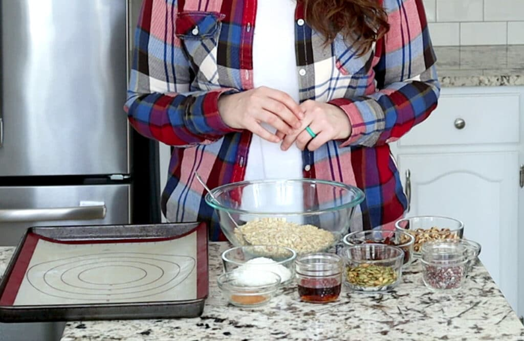 A person stands behind a marble counter covered with a large glass bowl filled with oats, surrounded by smaller glass bowls and jars filled with ingredients to make muesli (coconut, pumpkin seed, raisins, cinnamon and cacao nibs visible). A baking tray with silicone mat sits to the left. Person is wearing blue and red plaid shirt that is open with white t-shirt underneath and holds hands together at their waist.