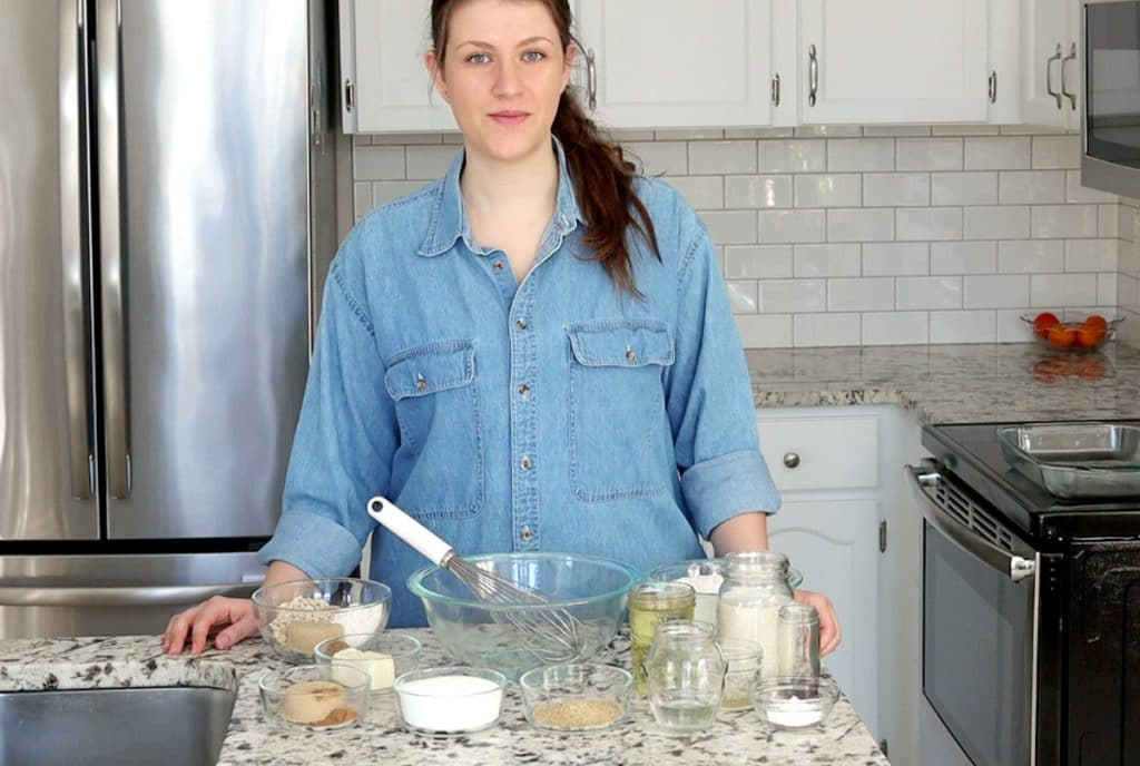 A fair skinned woman with dark brown hair pulled back in a ponytail wears a blue denim shirt and stands behind a marble countertop, looking at the camera with half a smile. The counter top has many small glass dishes each filled with a different ingredient, arranged around a large glass mixing bowl with a whisk sitting in it.
