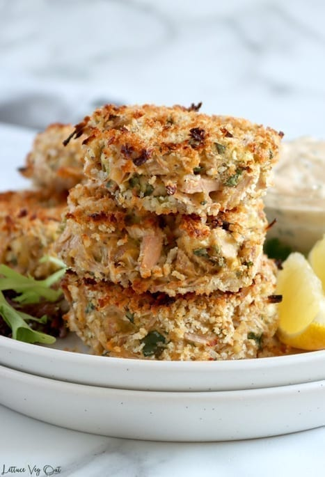 Front on view of a stack of three jackfruit crab cakes on a double stack of white plates. Two lemon wedges and a dish of creamy sauce sit on the plate to the right while a bit of leafy greens and two other crabless cakes sit to the left.