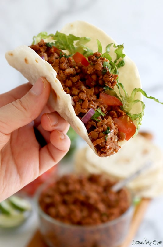 """Hand holding up folded flour tortilla filled with cooked walnut lentil taco """"meat"""" with chopped tomato, red onion and shredded lettuce. Blurred in the back is a glass bowl of walnut taco filling and stack of tortillas."""