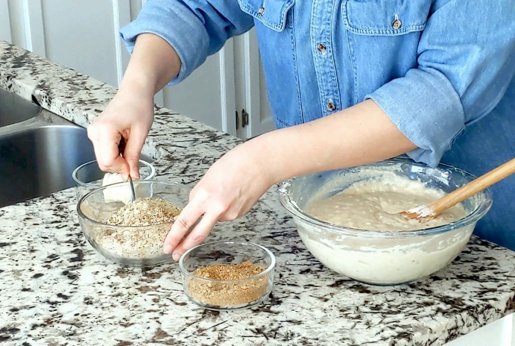 Hands stir together the dry contents of a medium sized glass bowl. A large bowl filled with cake batter and a wooden spoon sits to the right. Two other small glass dishes sit on the marble counter top.