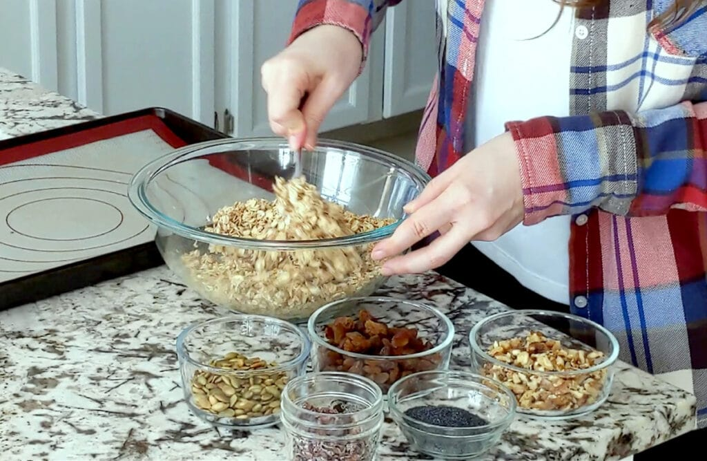 Person mixing a large glass bowl of oats and coconut. One hand holds the edge of the bowl while the other hand is blurry, in motion. Bowl on marble counter surrounded with small glass dishes filled with pumpkin seed, raisins, walnuts, poppy seed and cacao nibs. Baking tray with silicone mat to the top left side of image.