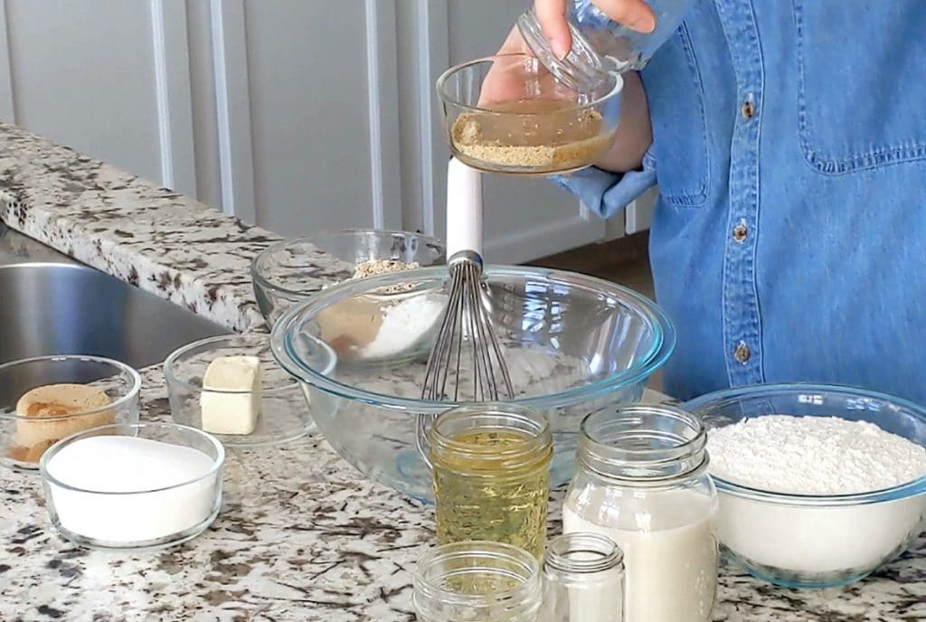 A marble countertop covered in small glass dishes and jars, filled with ingredients to make a cake. A hand holds up a small glass dish filled with ground flaxseed while the person's other hand pours water into the flaxseed.
