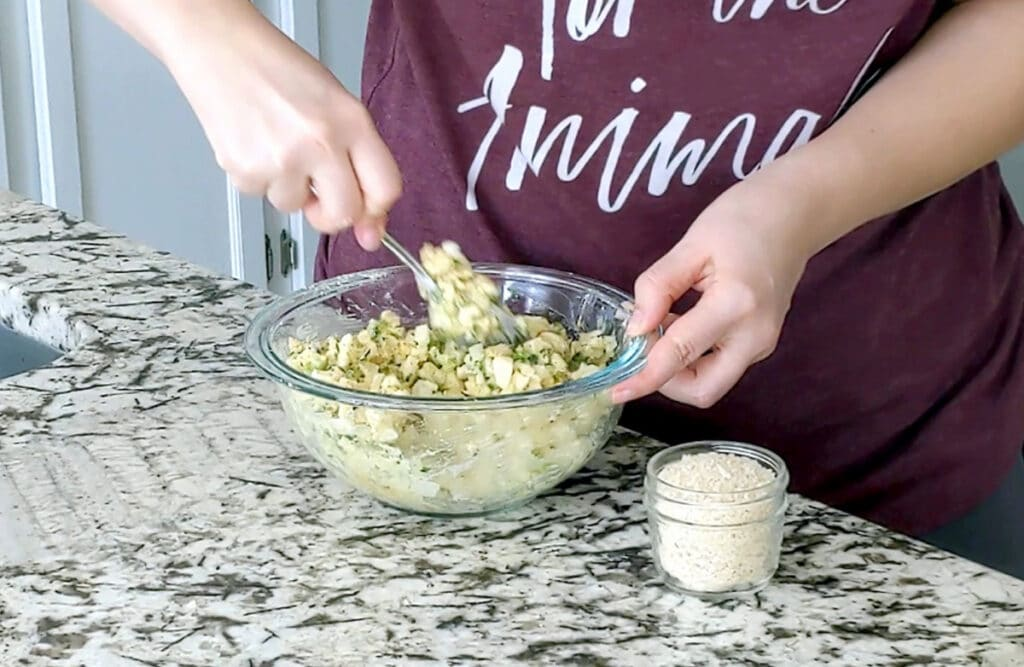 Person mixing ingredients in a large glass mixing bowl. One hand holds the edge of the bowl and the other is slightly blurred in motion. A small jar of breadcrumbs sits to the right of the mixing bowl.